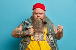 Strict bearded annoyed fisherman clenches fist angrily, looks with frowned face, uses fishing nets, keeps smoking pipe in mouth, wears yellow overalls, poses against blue background, works on boat