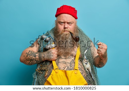 Strict bearded annoyed fisherman clenches fist angrily, looks with frowned face, uses fishing nets, keeps smoking pipe in mouth, wears yellow overalls, poses against blue background, works on boat Foto stock ©