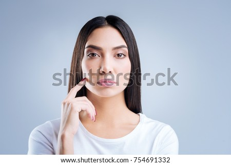 Strict employer. Young professional smart businesswoman looking strict and serious while standing against the blue background and listening to the workers of her company #754691332