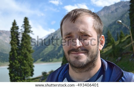 Strict face of a man with a beard in the mountains near the lake