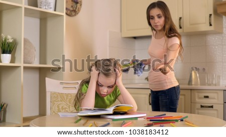 Strict mother criticizing daughter for mistakes in homework, lack of support