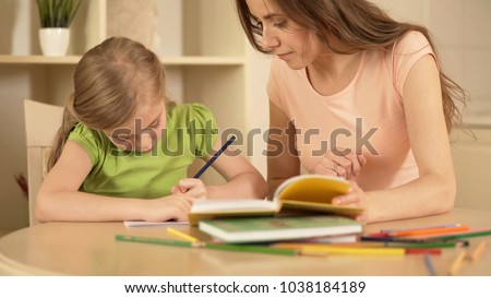 Strict mother watching her daughter doing homework helping her, home education #1038184189