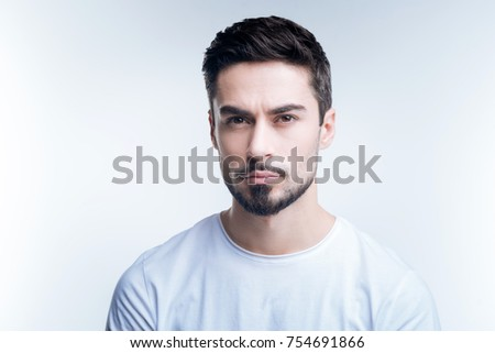 Strict person. Serious demanding young teacher looking strict while standing against the blue background and waiting for his students #754691866