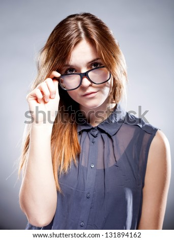 Strict serious young woman holding large nerd glasses