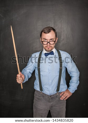 Strict teacher in eyeglasses with pointer on blackboard background ストックフォト ©