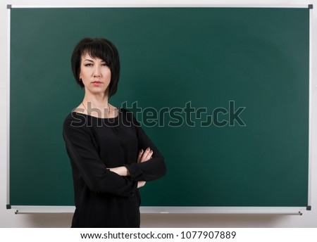 strict teacher posing by chalk Board, learning concept, green background, Studio shot #1077907889