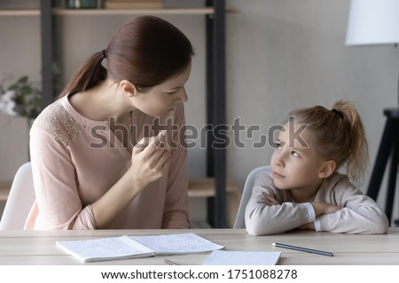 Strict young Caucasian mother studying with little schoolgirl daughter, scold lecture for bad marks, authoritative mom upbringing small daughter pupil, unmotivated to do homework, education concept ストックフォト ©
