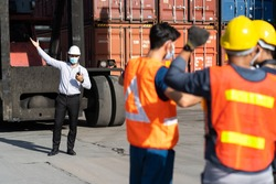 Strike of workers in container yard. Group of multiethnic engineer people during a protest in workplace