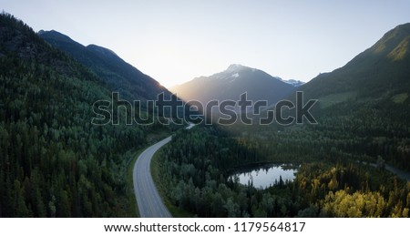 Striking aerial panoramic landscape view of a scenic road in the valley surrounded by the beautiful Canadian Mountains. Located near Revelstoke, BC, Canada. Stock foto ©