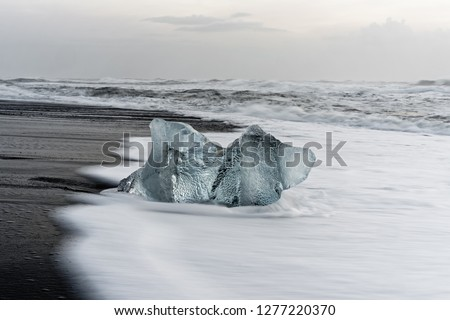 Striking block of ice in blue shades on a black beach with strong surf, spray on the dark sand, waves roll in the background - Location: Iceland, Jökulsarlon (Jökulsárlón) #1277220370