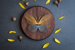 String art yellow blue butterfly on a brown wood with yellow flower petals