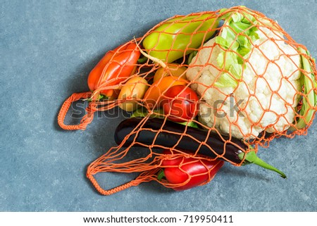 String bag with various fresh vegetables on blue textured background. Organic eco bio products from farm. New harvest. Ingredient in healthy, dietary and vegetarian food. Top view
