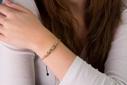 String bracelets designed with gold and beads on the arm of the young lady.