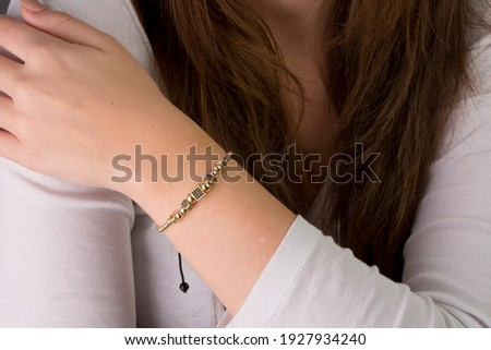 String bracelets designed with gold and beads on the arm of the young lady. Foto stock ©