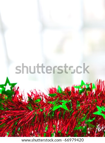 String of green and red christmas tinsel by a glass window