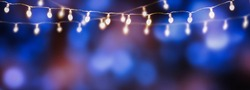 string of light bulbs on blue abstract background, fairy lights on bokeh party background at night, string of lights border