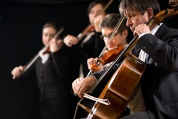 String orchestra performing on stage with cello on foreground.