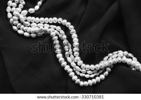 Strings of white pearl on black silk as a background #330710381