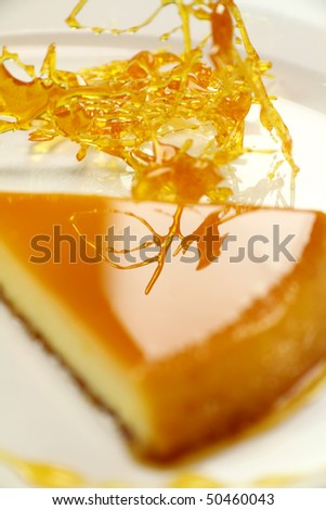 Stringy toffee reflected in the top of a slice of creme caramel dessert.