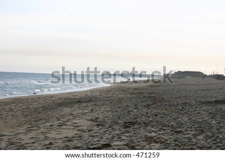 Strip of beach along the ocean at sunset