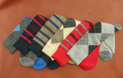 Striped and argyle men's dress socks. Made to wear with fancy attire and clothing, these footwear accessories are colorful and made of cotton and wool.