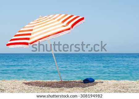 Shutterstock Striped beach umbrella on the beach.