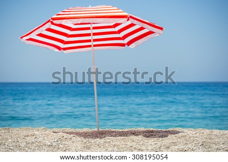 Striped beach umbrella on the beach. #308195054