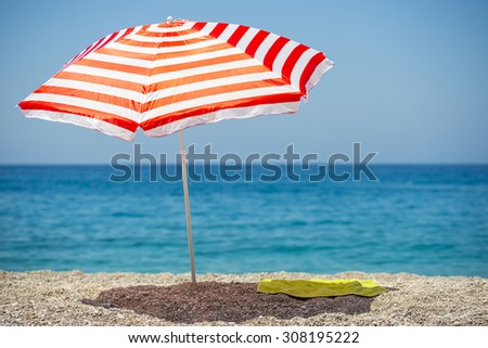 Striped beach umbrella on the beach. #308195222