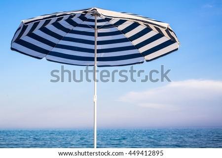Striped beach umbrella on the beach. #449412895