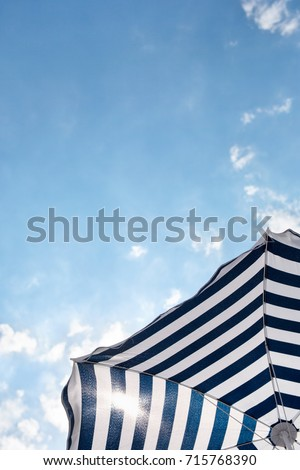 Striped beach umbrella on the beach on he background of sky #715768390