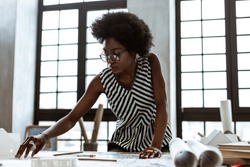 Striped blouse. African-American interior designer wearing striped blouse working hard in the office