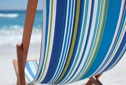 Striped blue deckchair on sandy beach, close up
