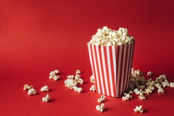 Striped box with popcorn on red background