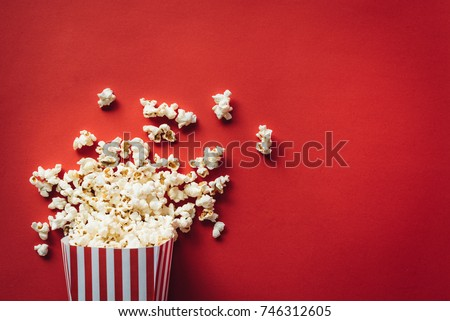 Striped box with popcorn on red background - Shutterstock ID 746312605
