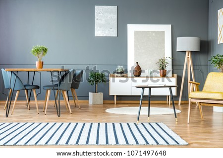 Striped carpet in grey apartment interior with chairs at dining table and paintings on the wall