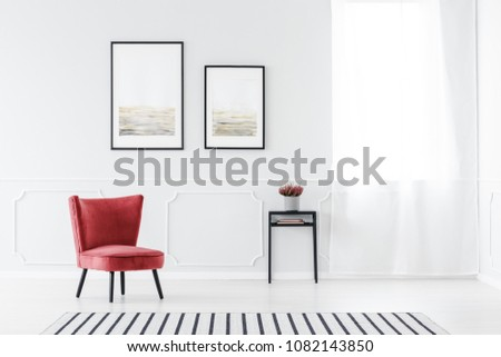 Striped carpet near red armchair in grey living room interior with posters on the wall next to window #1082143850