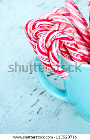 Striped Christmas candy canes in a light blue turquoise cup with shabby chic wooden background