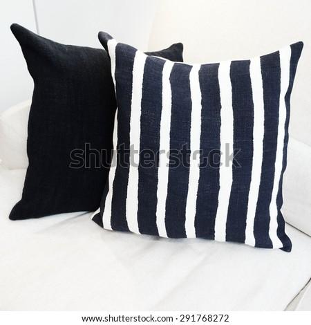 Striped cushion on a white sofa. Modern furniture.