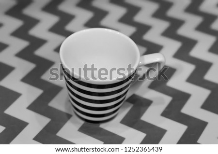 Striped espresso cup in a soft background with zigzag lines. #1252365439