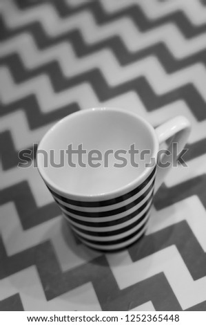 Striped espresso cup in a soft background with zigzag lines. #1252365448