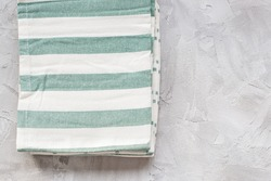 Striped green and white kitchen towels on gray background, top view, copy space