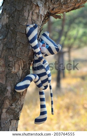 Striped handmade toy cat hanging on a tree
