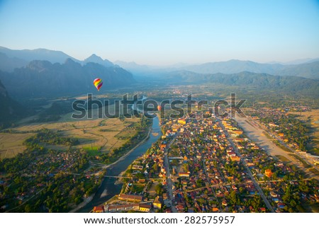 Striped hot air balloon flying over earth, evening landscape and the city with little houses, a river in Laos to Vang Vieng.Laos.