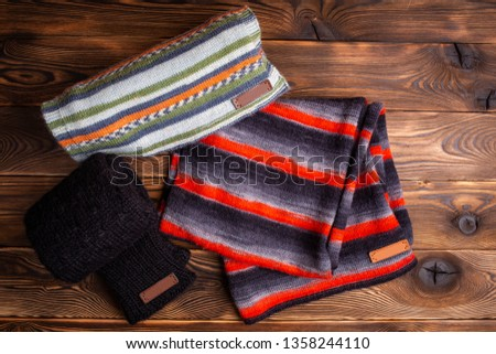 striped knit striped scarves and black knitted sleeves on wooden background #1358244110