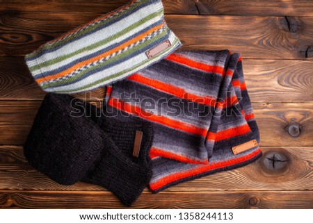 striped knit striped scarves and black knitted sleeves on wooden background #1358244113