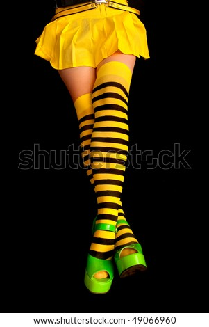striped legs - yellow and black stripes, green shoes, on black background
