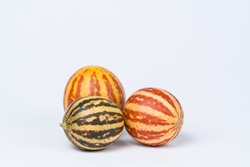 Striped little decorative pumpkins on a white background