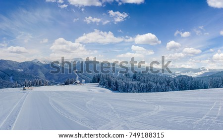 Striped prepared ski slope on a background of mountain ranges and sky on ski resort in Carpathian Mountains\r