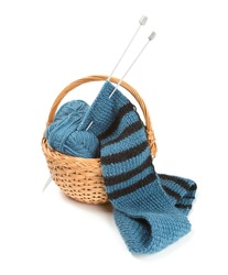 striped scarf on knitting needles over white