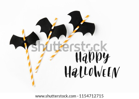 Striped straws with paper bats on white background. Halloween holiday decorations. Flat lay, top view